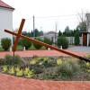 Kríž medzi kostolom a farou. Tento kríž mal byť súčasťou jedného zastavenia Krížovej cesty- Šimon z Cyrény pomáha Pánu Ježišovi niesť kríž. Chýbajú tu postavy aj Krista Pána, aj Šimona.